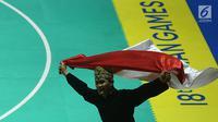 Pesilat Indonesia Sugianto membawa bendera merah putih usai meraih medali emas dalam babak final tunggal putra pencak silat seni Asian Games 2018 di Padepokan Pencak Silat Taman Mini Indonesia Indah (TMII), Jakarta, Rabu (29/8). (Merdeka.com/ Imam Buhori)
