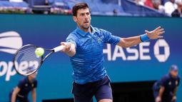 Petenis Serbia, Novak Djokovic mengembalikan bola ke arah lawannya Roberto Carballes Baena dari Spanyol pada  babak pertama AS Terbuka 2019 di Billie Jean King National Tennis Center, New York, Senin (26/8/2019). Unggulan pertama itu memetik kemenangan 6-4, 6-1, 6-4. (AP/Frank Franklin II)