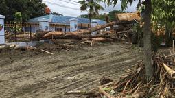 Sebuah alat berat berusaha mengevakuasi puing-puing dan batang pohon yang tumbang asca banjir bandang di Kabupaten Sentani, Jayapura, (17/3). Banjir bandang Sentani menewaskan 70 orang dan puluhan luka-luka. (AFP/Netty Dharma Somba)