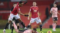 Striker Manchester United Anthony Martial melanggar pemain Sheffield United Phil Jagielka dalam lanjutan Liga Inggris di Old Trafford, Kamis (28/1/2021). (AP Photo/Laurence Griffiths,Pool)