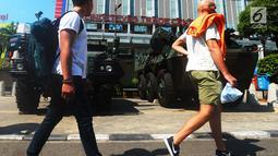 Pejalan kaki melintas di depan kendaraan lapis baja TNI di pertokoan Glodok, Jakarta, Jumat (11/5). Aksi Bela Palestina tersebut sebagai protes atas pemindahan Kedubes AS dari Tel Aviv di Israel ke kota Yerusalem di Palestina. (Merdeka.com/Imam Buhori)
