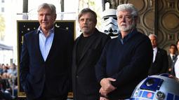 Mark Hamill (tengah) berfoto bersama Harrison Ford (kiri) dan George Lucas (kanan) saat dianugerahi Hollywood Walk of Fame di Los Angeles (8/3). Yang menarik, seremoni acara dilakukan dengan tema Star Wars. (Jordan Strauss / Invision / AP)