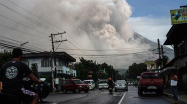 Pengendara melintasi jalanan ketika gunung Mayon mengeluarkan gumpalan asap raksasa di Camalig, selatan Manila, Senin (22/1). Filipina menaikkan Status Gunung Mayon menjadi level 4 setelah memuntahkan abu vulkanis setinggi 10 kilometer. (AFP PHOTO/STR)
