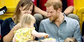 Pangeran Harry membuat wajah menggemaskan saat seorang anak mencuri popcornnya di Invictus Games, 2017. (Samir Hussein/WireImage)