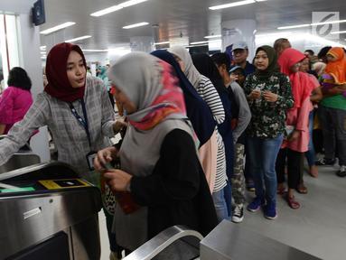 Petugas membantu calon penumpang melakukan tap kartu saat akan menggunakan layanan transportasi Moda Raya Terpadu (MRT) di Stasiun Bundaran HI, Jakarta, Rabu (3/4). Meski sudah tidak digratiskan, warga tetap antusias menjajal MRT. (merdeka.com/Imam Buhori)