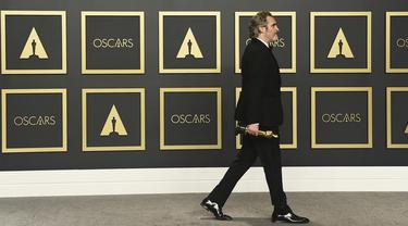 Aktor Joaquin Phoenix berjalan membawa piala Oscar 2020 usai berpose di ruang pers di  Dolby Teater, Los Angeles, Minggu (9/2/2020). Joaquin Phoenix yang memerankan karakter Arthur Fleck dalam film Joker, meraih penghargaan Oscar 2020 untuk kategori aktor terbaik. (AP Photo/Jordan Strauss)