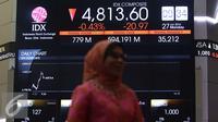 Pengunjung melintasi layar di Bursa Efek Indonesia, Jakarta, Senin (27/6). Laju Indeks Harga Saham Gabungan (IHSG) melemah pada perdagangan Senin (27/6). (Liputan6.com/Angga Yuniar)