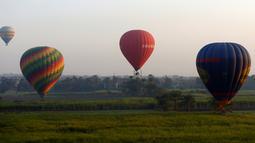 """Sejumlah balon udara panas yang membawa wisatawan mengudara di atas kota Luxor, Kairo, Mesir (13/12). Kota Luxor dijuluki sebagai """"The World Greatest Open Air Museum"""". (Reuters/Amr Abdallah Dalsh)"""