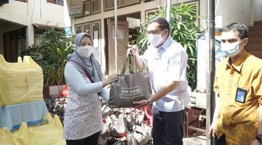 Pemimpin BNI Wilayah Manado Koko Prawira Butar-Butar menyerahkan secara simbolis bantuan kemanusiaan di Manado, Sulawesi Utara, Selasa (19 Januari 2021).