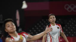 Ganda putri Indonesia Greysia Polii (kanan) dan Apriyani Rahayu saat melawan Yuki Fukushima dan Sayaka Hirota dari Jepang pada penyisihan Grup A bulu tangkis Olimpiade Tokyo 2020 di Musashino Forest Sports Plaza, (27/7/2021). Greysia / Apriyani menang 24-22, 13-21, dan 21-8. (Alexander NEMENOV/AFP)