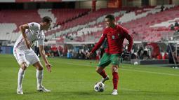 Bek Prancis, Benjamin Pavard berusaha memblokir penyerang Portugal, Cristiano Ronaldo pada babak penyisihan Liga A Grup 3 UEFA Nations League di Estadio da Luz, Lisbon, Minggu (15/11/2020) dinihari WIB. Prancis lolos ke semifinal usai mengalahkan tim kandang Portugal 1-0. (AP Photo/Armando Franca)