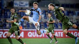 Penyerang Lazio, Ciro Immobile, berebut bola dengan bek Cagliari, Ragnar Klavan, pada laga lanjutan Serie A pekan ke-35 di Stadio Olimpico, Jumat (24/7/2020) dini hari WIB. Lazio menang 2-1 atas Cagliari.(AFP/Filippo Monteforte)