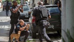 Para polisi militer Rio de Janeiro mengambil posisi saat melakukan operasi penggerebekan di daerah kumuh Cidade de Deus di Rio de Janeiro, Brasil (1/2). (AFP Photo/Mauro Pimentel)