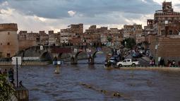 Sejumlah warga melihat jalanan yang terendam banjir di Sanaa, Yaman, Selasa (2/8). Hujan lebat yang mengguyur Sanaa membuat salah satu ruas jalan di kota itu berubah seakan menjadi sungai. (REUTERS / Khaled Abdullah)