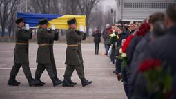 Prajurit Penjaga Kehormatan membawa jenazah 11 warga Ukraina yang tewas dalam insiden jatuhnya pesawat Ukraine International Airlines di Iran (8/1) lalu, Bandara Boryspil Kiev, Ukraina, Minggu (19/1/2020). 176 penumpang dan awak tewas dalam tragedi tersebut.(Ukrainian Presidential Press Service/AFP)