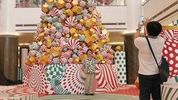 Pengunjung berfoto di depan pohon Natal yang menghiasi pusat perbelanjaan di kawasan Menteng, Jakarta, Minggu (23/12). Konsep dekorasi pohon Natal modern disajikan untuk membuat suasana berbeda dari tahun-tahun sebelumnya. (Liputan6.com/Herman Zakharia)