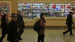 Orang-orang berjalan melewati toko mainan di stasiun kereta bawah tanah Kaeson, Pyongyang, Korea Utara (23/11/2019). Stasiun ini diperbaharui pada tahun 2019 dengan pencahayaan baru dan TV untuk menghibur penumpang yang menunggu. (AP Photo/Dita Alangkara)
