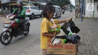 Seorang anak mengambil mi instan dan telur gratis di Jalan Raya Cibubur-Bojong Kulur, Bogor, Kamis (9/4/2020). Di beberapa pinggir jalan Kawasan Jabotabek saat ini banyak aksi solidaritas oleh warga dengan menyediakan bahan makanan gratis di tengah pandemi virus corona. (merdeka.com/Arie Basuki)