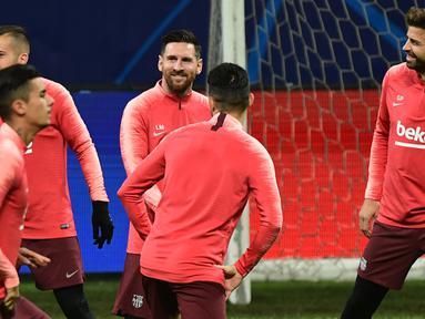 Pemain Barcelona, Lionel Messi (tengah) bercanda dengan rekan setimnya, Jordi Alba dan Gerard Pique selama sesi latihan menjelang laga lanjutan Grup B Liga Champions menghadapi Inter Milan di stadion San Siro, Senin (5/11). (Miguel MEDINA/AFP)