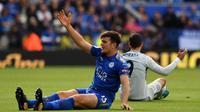 Bek Leicester, Harry Maguire, terjatuh saat berebut bola dengan striker Chelsea, Alvaro Morata, pada laga Premier League di Stadion King Power, Leicester, Sabtu (9/9/2017). Leicester kalah 1-2 dari Chelsea. (AFP/Ben Stansall)