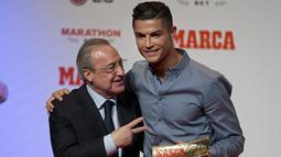 Cristiano Ronaldo memeluk presiden Real Madrid, Florentino Perez  usai mandapat ucapan selamat setelah meraih penghargaan Marca di Reina Victoria Theater, Madrid (29/7/2019). Bersama Madrid, Ronaldo menjadi topskor sepanjang masa klub dengan 450 gol dalam 438 penampilan. (AP Photo/Paul White)