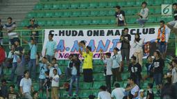 Suporter Laskar Joko Tingkir membentangkan spanduk bertuliskan nama alm Choirul Huda saat menyaksikan laga Persela melawan Bhayangkara FC di Stadion Patriot Candrabhaga, Bekasi, Jumat (27/10). (Liputan6.com/Helmi Fithriansyah)