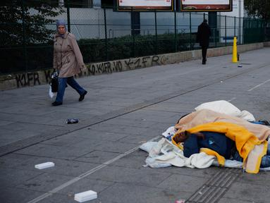 Pejalan kaki berjalan dekat para imigran yang tidur di jalanan Kota Paris, Prancis, Rabu (6/11/2019). Gelombang imigran membanjiri Prancis akibat konflik dan kemiskinan di Asia, Timur Tengah, dan Afrika sejak 2015. (AP Photo/Francois Mori)