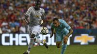 Eric Bailly (kiri) membela Manchester United (kiri) pada laga melawan Barcelona di tur pramusim. (AP Photo/Larry French)