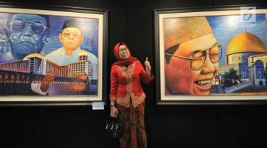 """Pelukis Nabila Dewi Gayatri berpose di antara dua karyanya yang dipamerkan dalam """"Sang Maha Guru"""" di Jakarta, Kamis (22/11). Pameran ini menampilkan 29 lukisan yang  menggambarkan sosok KH Abdurrahman Wahid atau Gus Dur. (Merdeka.com/Iqbal Nugroho)"""