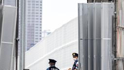 Seorang petugas polisi berjaga di pintu masuk kawasan wisma atlet Olimpiade dan Paralimpiade Tokyo 2020, di Tokyo pada Rabu (14/7/2021). Pembukaan pesta olahraga terbesar di dunia itu tinggal menghitung hari di tengah pandemi COVID-19. (Behrouz MEHRI / AFP)