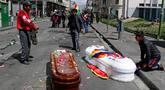 Peti mati berisi jenazah orang yang tewas dalam bentrokan antara pasukan keamanan dengan pendukung mantan Presiden Evo Morales tergeletak di tengah jalan setelah polisi meluncurkan gas air mata pada prosesi pemakaman besar-besaran di El Paz, Bolivia, Kamis (21/11/2019). (AP Photo/Juan Karita)
