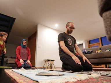 Ahmad Kamel (depan) melaksanakan salat Maghrib dengan istrinya, Nadia Chaouch, ketika putra mereka Ahmad Kamel berlari melewati setelah keluarga berbuka puasa saat bulan Ramadan selama wabah Covid-19 di rumah mereka di Seattle (28/4/2020). (AP/Elaine Thompson)