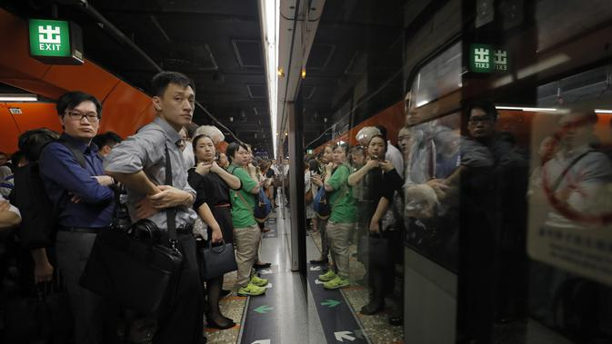 Penumpang mengantre di platform kereta bawah tanah di Hong Kong, Selasa (30/7/2019). Para pengunjuk rasa telah mengganggu layanan kereta bawah tanah pada pagi hari perjalanan dengan menghalangi pintu-pintu masuk kereta dan mencegah mereka meninggalkan stasiun. (AP Photo/Vincent Yu)