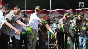 Polisi memusnahkan minuman keras (miras) di Polres Gorontalo, Gorontalo, Jumat (4/1). Miras yang dimusnahkan sebanyak puluhan ribu liter. (Liputan6.com/Arfandi Ibrahim)