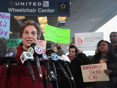 Perwakilan demonstran menyampaikan orasinya di depan terminal United Airlines terkait pengusiran penumpang di pesawat United Airlines di Bandara Internasional O'Hare, Chicago, AS, Selasa (11/4). (Scott Olson / Getty Images / AFP)
