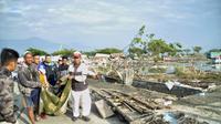 Warga mengevakuasi kantong jenazah berisi jasad korban tsunami di Palu, Sulawesi Tengah , Sabtu (29/9). Gelombang tsunami setinggi 1,5 meter yang menerjang Palu terjadi setelah gempa bumi mengguncang Palu dan Donggala. (AP Photo/Rifki)