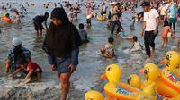 Seorang ibu berjalan di dekat pelampung berbentuk bebek di Pantai Karnaval Ancol, Jakarta, Sabtu (16/6). H+1 libur Lebaran, jumlah pengunjung di Ancol mencapai 88.143 orang. (Liputan6.com/Immanuel Antonius)