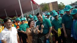 Menteri Koordinator Bidang Kemaritiman Luhut Binsar Panjaitan berfoto bersama seorang warga saat menggelar gerakan aksi bersih di kawasan pesisir Cilincing, Jakarta Utara, Sabtu (6/4). (Liputan6.com/Immanuel Antonius)