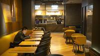 Seorang pria mengenakan masker menunggu makanannya di sebuah restoran di pusat perbelanjaan Beijing (28/1/2020). Jumlah korban meninggal dunia di Provinsi Hubei, China tengah, akibat Virus Corona bertambah 65 orang. (AP Photo/Mark Schiefelbein)