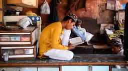 Seorang anak membaca Alquran di sebuah toko yang tutup selama bulan Ramadan saat penerapan lockdown di New Delhi, Senin (4/5/2020). Di emperan toko-toko yang tutup, umat muslim melaksanakan salat jemaah dengan menjaga jarak aman dan beberapa lainnya membaca kitab suci Alquran. (Sajjad HUSSAIN/AFP)