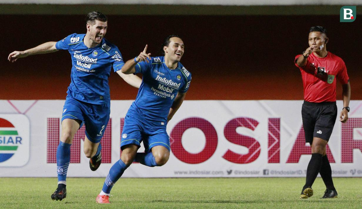 Striker Persib Bandung, Ezra Walian (kanan) melakukan selebrasi usai mencetak gol pertama timnya ke gawang Persebaya Surabaya dalam laga perempatfinal Piala Menpora 2021 di Stadion Maguwoharjo, Sleman, Minggu (11/4/2021). (Bola.com/M Iqbal Ichsan)