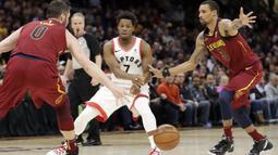 Pemain Toronto Raptors, Kyle Lowry (tengah) melakukan umpan melewati adangan dua pemain Cleveland Cavaliers pada lanjutan NBA basketball game di Quicken Loans Arena, (21/3/2018) Cleveland. Cavs menang 132-129. (AP/Tony Dejak)