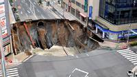 Sebuah lubang raksasa atau yang biasa disebut sinkhole tiba-tiba muncul di persimpangan dekat Stasiun Hakata, Fukuoka, Jepang, Selasa (8/11). Jalanan itu tiba-tiba runtuh hingga menciptakan lubang besar dan menghebohkan warga sekitar. (Kyodo/via REUTERS)