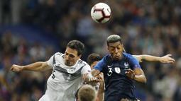 Pemain Prancis, Presnel Kimpembe, duel udara dengan bek Jerman, Mats Hummels, pada laga UEFA Nations League di Stade de France, Paris, Selasa (16/10/2018). Prancis menang 2-1 atas Jerman. (AP/Christophe Ena)