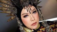 """Penyanyi asal Bandung ini kembali mengenakan headpiece yang bertajuk """"Matahari"""" berwarna emas dan hitam karya Rinaldy Yunardi, lengkap dengan rumbai berwarna perak yang memperindah kepalanya. (Liputan6.com/IG/@melly_goeslaw)"""