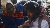 Personel Polisi Wanita (Polwan) Polres Jakarta Timur yang mengenakan busana kebaya, membantu mengenakan helm kepada penggendara motor ketika mengatur arus lalu lintas di Jalan Otista Raya, Jatinegara, Jakarta, Jumat (20/4). (Merdeka.com/Imam Buhori)