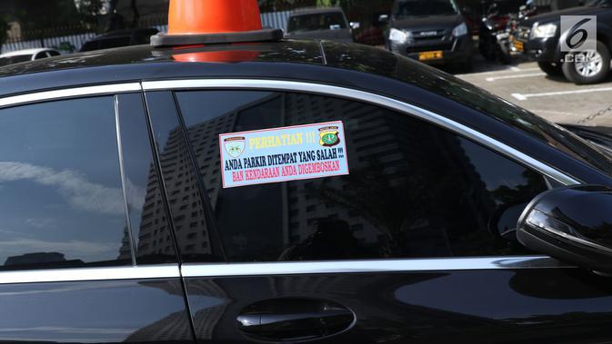 Stiker sanksi tertempel di mobil yang parkir di halaman Polda Metro Jaya, Senin (19/11). Polda Metro Jaya menerapkan sanksi penggembosan dan penempelan stiker bagi kendaraan yang parkir sembarangan di halaman Polda Metro. (Liputan6.com/Helmi Fithriansyah)