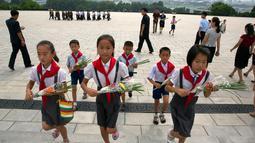 Anak-anak membawa bunga saat akan memberi penghormatan kepada patung pemimpin Korea Utara Kim Il Sung dan Kim Jong Il dalam peringatan berakhirnya Perang Dunia II dan pembebasan dari kolonial Jepang di Pyongyang, Korut, Rabu (15/8). (AP Photo/Ng Han Guan)