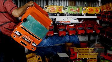 Sebuah mainan mobil kayu ditawarkan di kios mainan kayu di kawasan Kalibata, Jakarta (27/5/2015). Produksi mainan lokal dan tradisional diharapkan mampu bertahan, mengingat pasar bebas Asean yang dimulai Januari 2016 mendatang. (Liputan6.com/Johan Tallo)
