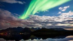 Pemandangan saat aurora borealis menghiasi langit Reinfjorden di Reine, di Kepulauan Lofoten, Lingkaran Arktik (8/9). Aurora menampilkan banyak warna, tetapi yang paling sering muncul adalah warna hijau muda dan pink. (AFP Photo/Jonathan Nackstrand)